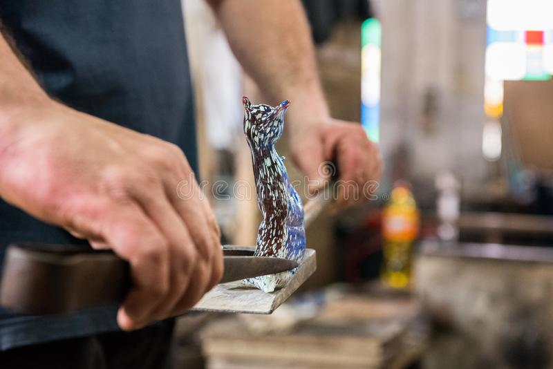 Glass Maker and Cat. Professional glass maker crafts a cat from one piece of glass royalty free stock photo