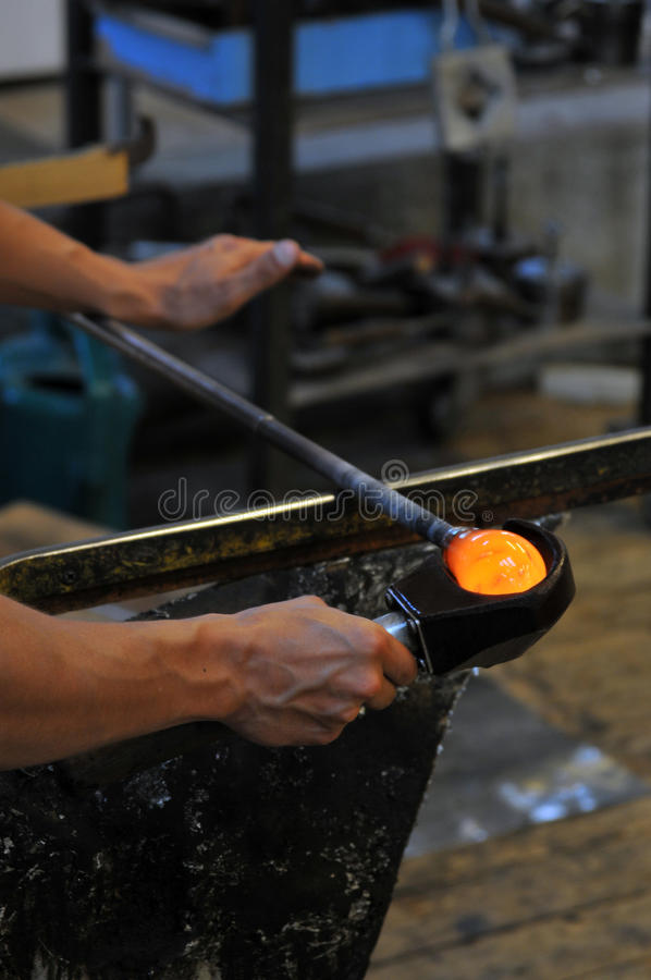 Glass making factory. Worker in a glass making factory royalty free stock image