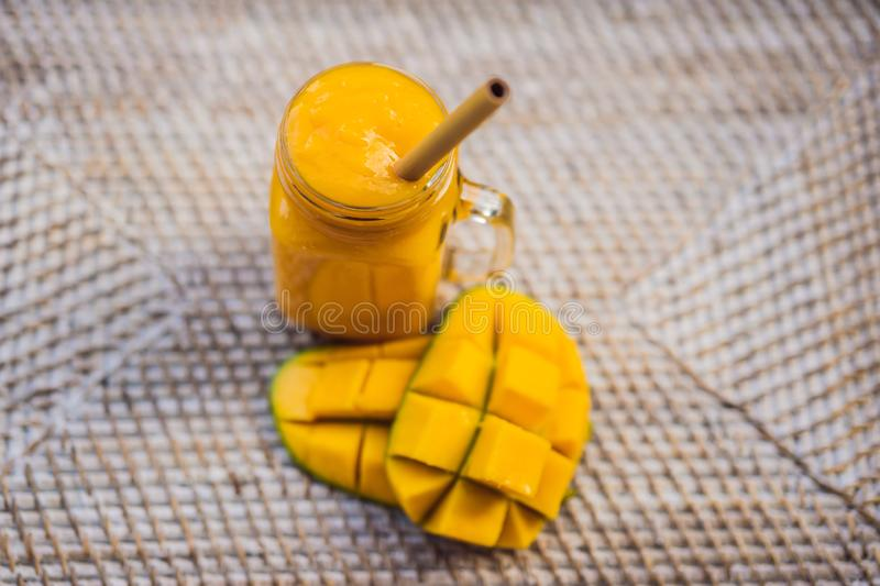 Glass of mango smoothie with bamboo drinking straw. Exotic vacation, chill out drink concept.  stock photo