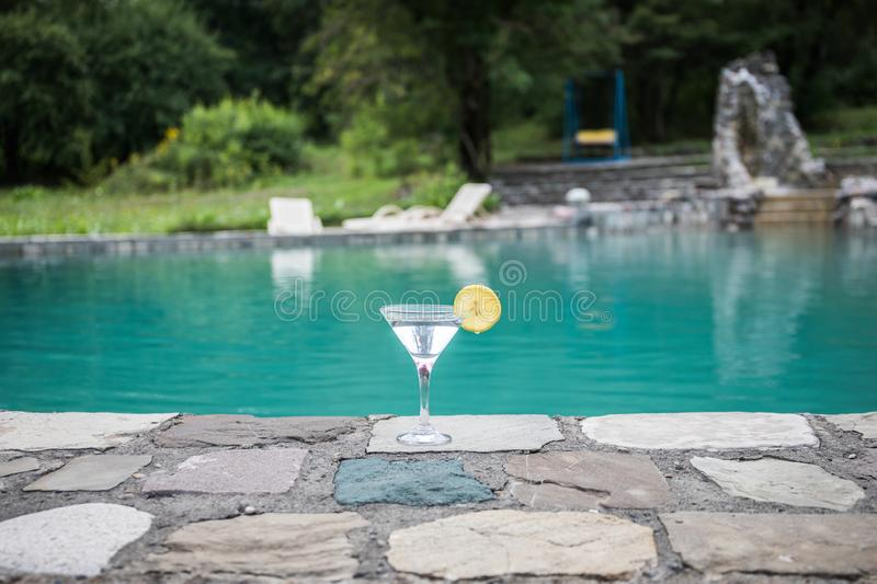 Glass of martini cocktail at swimming pool with ocean and palm tree background. A glass of blue martini cocktail welcome drink bar stock photo