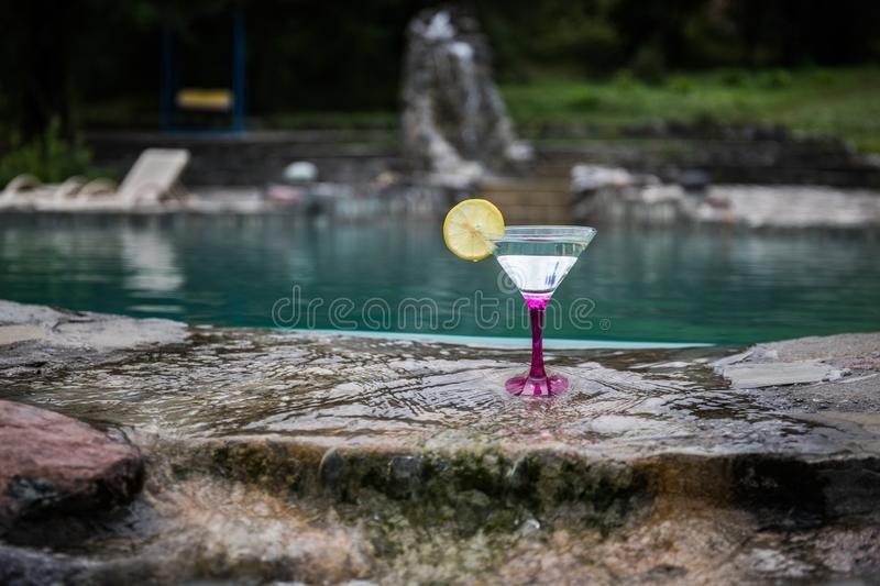 Glass of martini cocktail at swimming pool with ocean and palm tree background. A glass of blue martini cocktail welcome drink bar stock photography