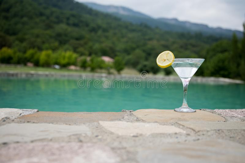 Glass of martini cocktail at swimming pool with ocean and palm tree background. A glass of blue martini cocktail welcome drink bar stock image