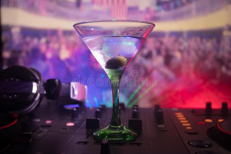 Glass with martini with olive inside on dj controller in night club. Dj Console with club drink at music party in nightclub with d. Isco lights royalty free stock image