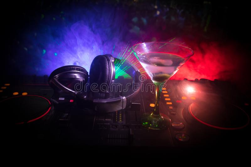 Glass with martini with olive inside on dj controller in night club. Dj Console with club drink at music party in nightclub with d stock photos