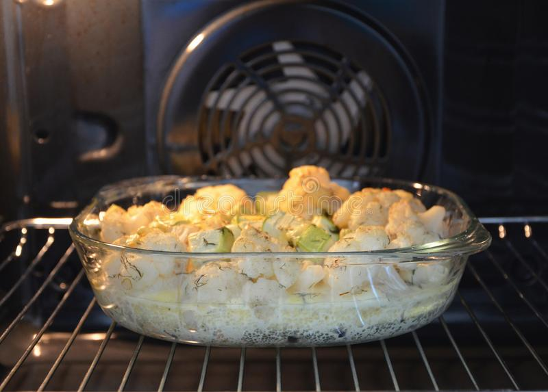 Glass maträtt med grönsaker i ugnen arkivfoto