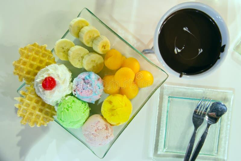 Glass med bäret, piskar kräm- som tjänas som med bananen, dillande och royaltyfria foton