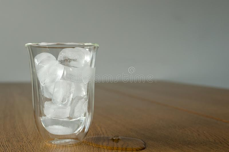 Glass with melting ice pieces and one piece of ice on the wooden table. Ice is partially melted. Copyspace for text, background royalty free stock photography