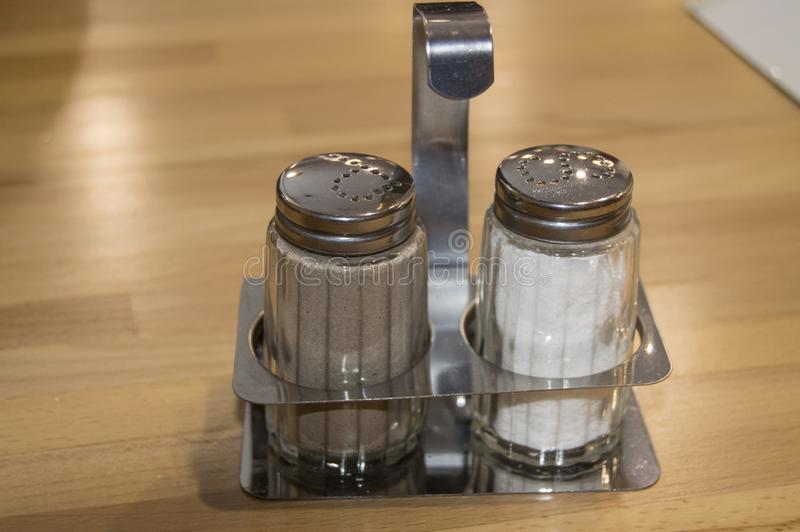 Glass and metal set salt and pepper shaker on a wooden table in a cafe, close-up stock images