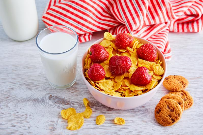 Glass of milk, a bowl of dry cereal corn flakes with strawberry topping and chocolate chip cookies on a wooden table royalty free stock images