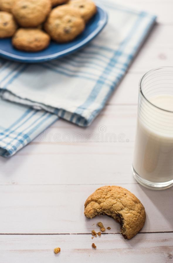 A glass of milk and a cookie with a bite taken out of it next to stock photography