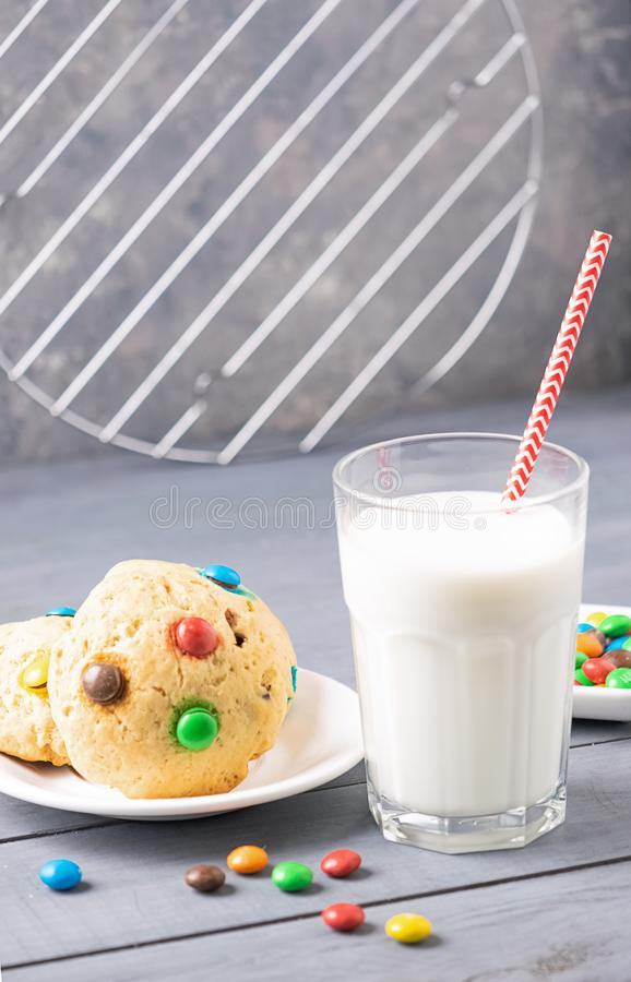 A glass of milk and cookies decorated with colorful jelly beans candies gray background. Children`s breakfast snack. A glass of milk and homemade cookies royalty free stock photography