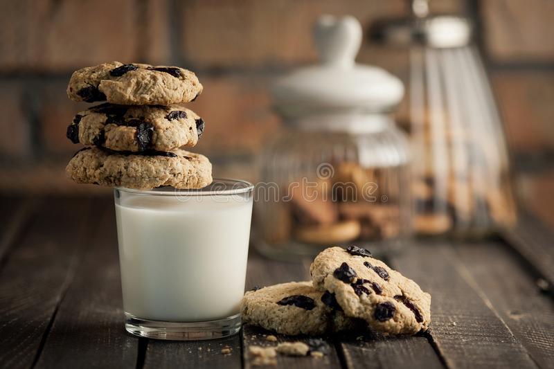A glass of milk and cookies with raisins. A wooden table and a brick wall on a background. Selective focus. royalty free stock photography