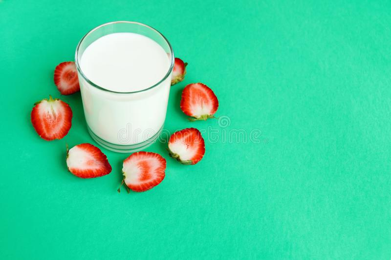 Glass of milk and halves of strawberry around on a turquoise background, top view. royalty free stock images
