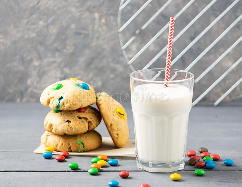 A glass of milk and homemade cookies decorated with colorful jelly beans candies. Children`s breakfast snack. A glass of milk and homemade cookies decorated royalty free stock photos
