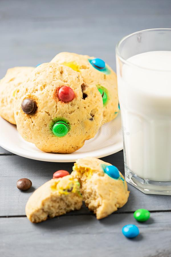 A glass of milk and homemade cookies decorated with colorful jelly beans candies. Children`s breakfast snack. Vertical frame stock photography