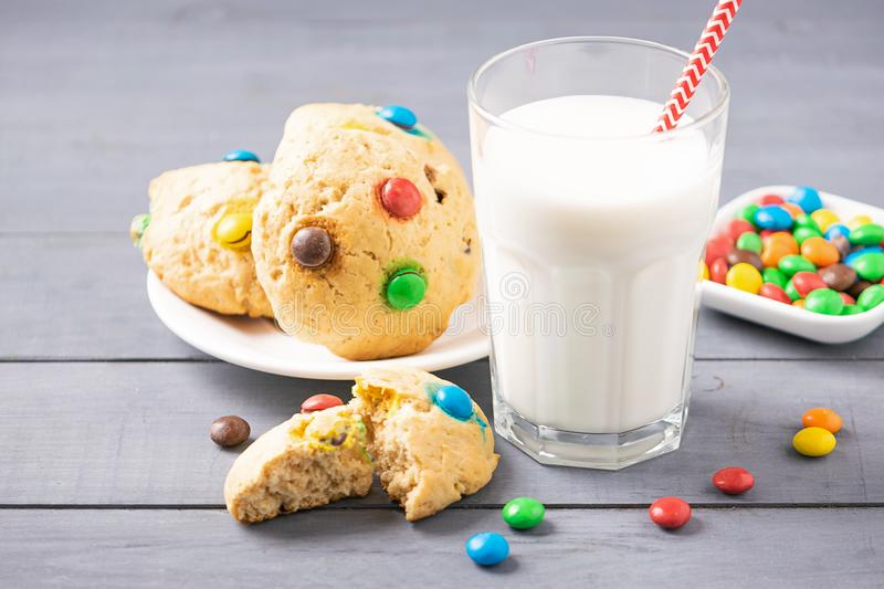 A glass of milk and homemade cookies decorated with colorful jelly beans candies. Children`s breakfast snack. A glass of milk and homemade cookies decorated royalty free stock photo