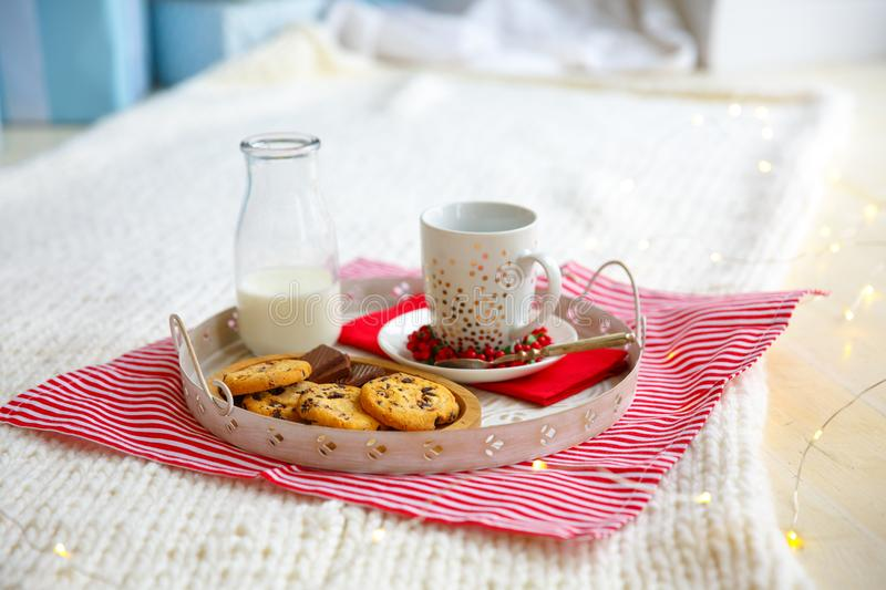Glass with milk and oatmeal cookies with chocolate chips close-up on white tray stock photo