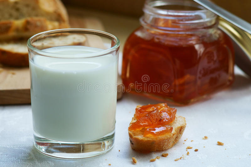 A glass of milk with a piece of bread and jam. stock image