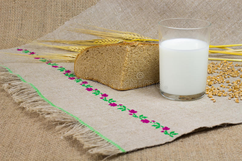 Glass of milk, a quarter of bread, wheat ears stock photography