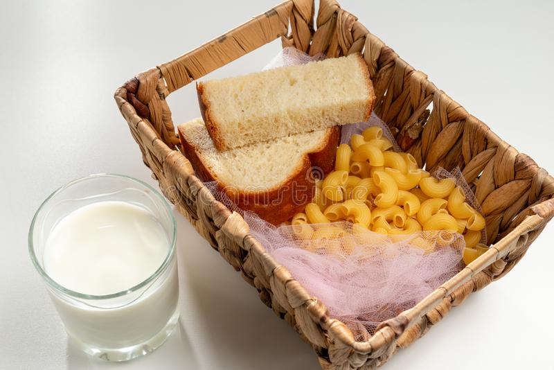 Glass of milk and wooden basket with food are on the white background/table. International Day to Assist the Poor royalty free stock image