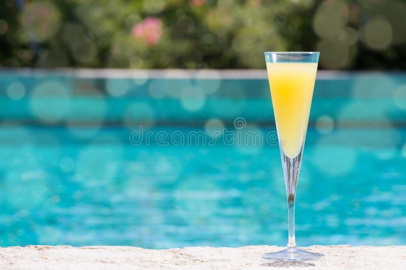 Glass of Mimosa. Cocktail on the pool nosing at the tropical resort. Horizontal, cocktail on right side. Bokeh details royalty free stock photography
