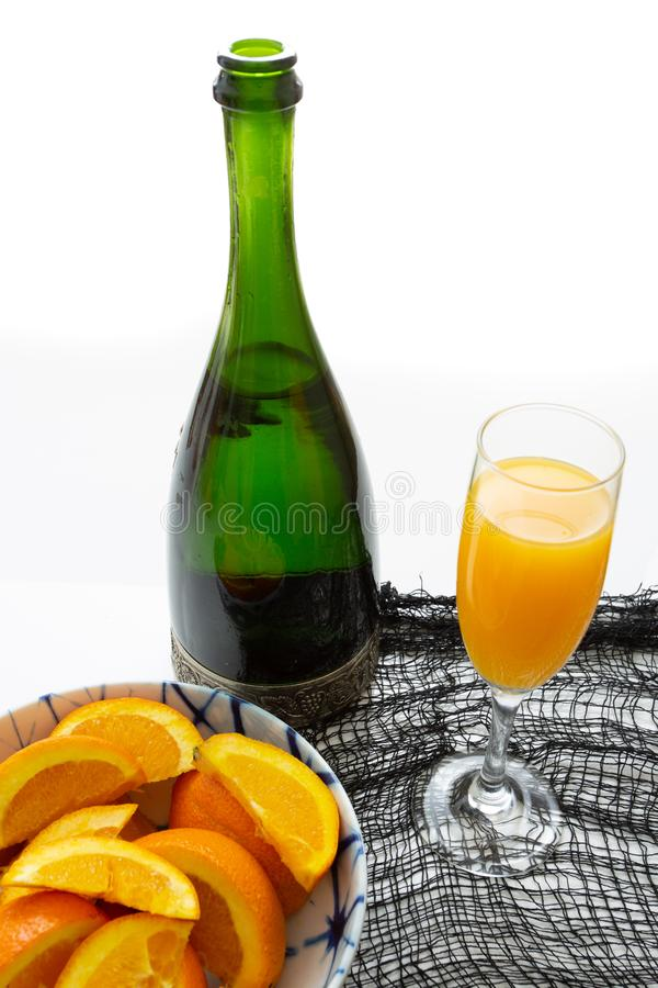 Glass of mimosa cocktail ready to be served for brunch with an orange slice with a champagne bottle and a bowl of orange slices on stock image