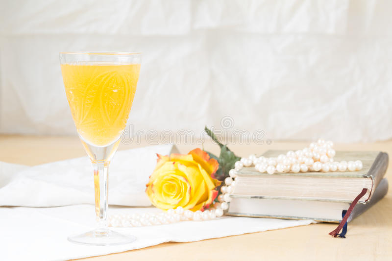 Glass of mimosa cocktail with vintage books and pearls stock photography