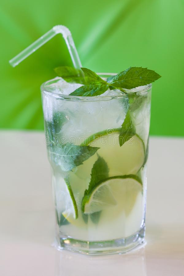 A glass of mint lemonade. Cold fresh drink on green beige background. Shallow depth of field.  stock photos