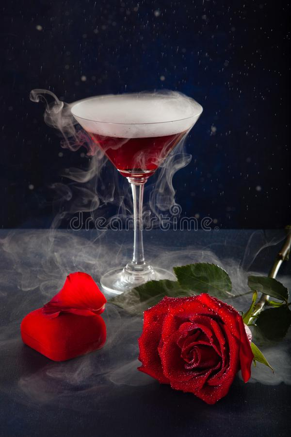 Glass of mistic drink, rose and box with a ring royalty free stock photo