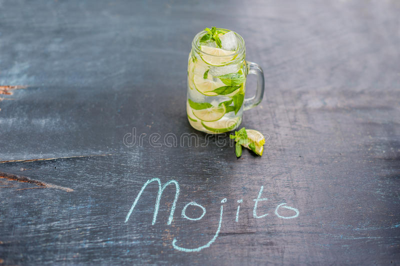 Glass of mojito with lime and mint ice cube close-up on dark wood background. The inscription in chalk MOJITO royalty free stock photos