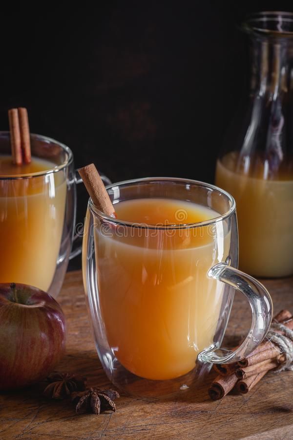 Glass Mug of Apple Cider. With cinnamon stick on a rustic wooden surface and dark background stock images