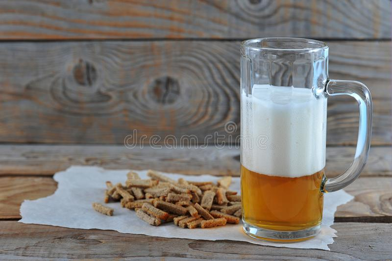 Glass mug with beer with foam, snack crackers stock photo