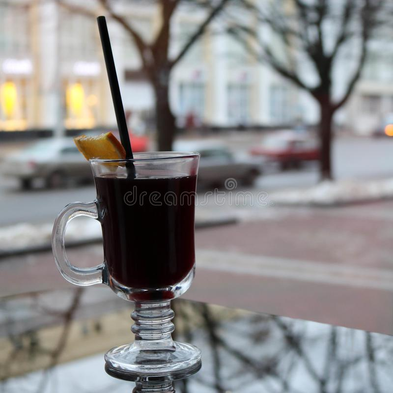 Glass mug with brown, tasty, hot, fragrant, alcoholic mulled wine with a slice of lemon and a straw on the table in a cafe in the. Evening in the background of royalty free stock photo