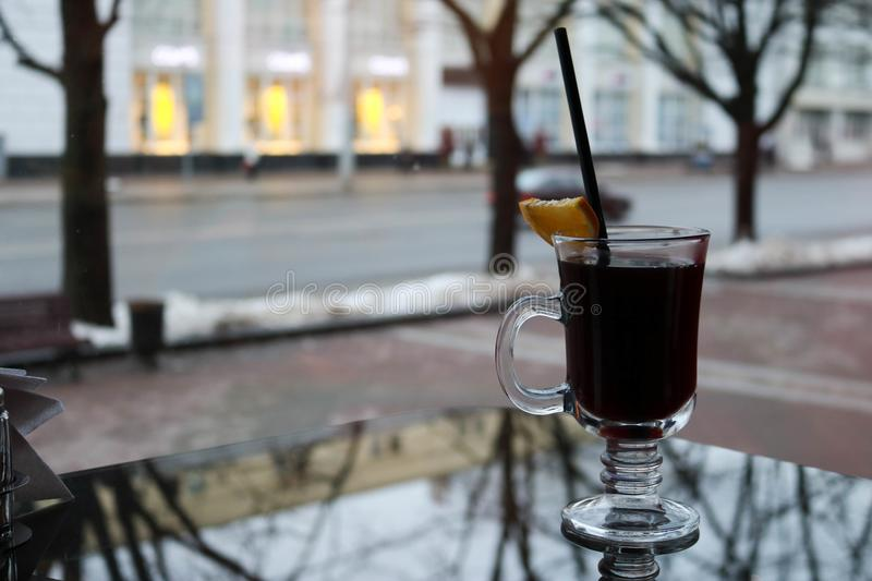 Glass mug with brown, tasty, hot, fragrant, alcoholic mulled wine with a slice of lemon and a straw on the table in a cafe in the. Evening in the background of stock photos