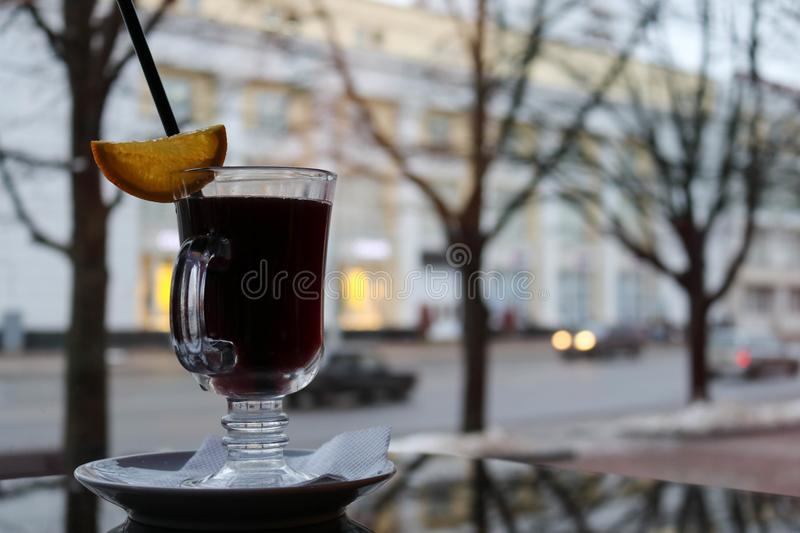 Glass mug with brown, tasty, hot, fragrant, alcoholic, warm mulled wine on a table in a cafe in the evening. Against a window in the evening royalty free stock images