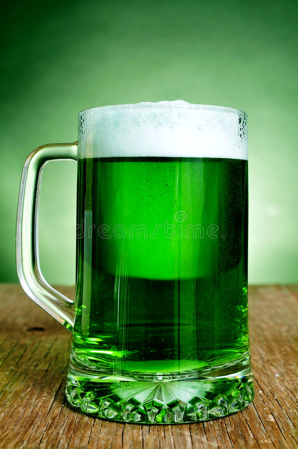 Glass mug with dyed green beer stock photo