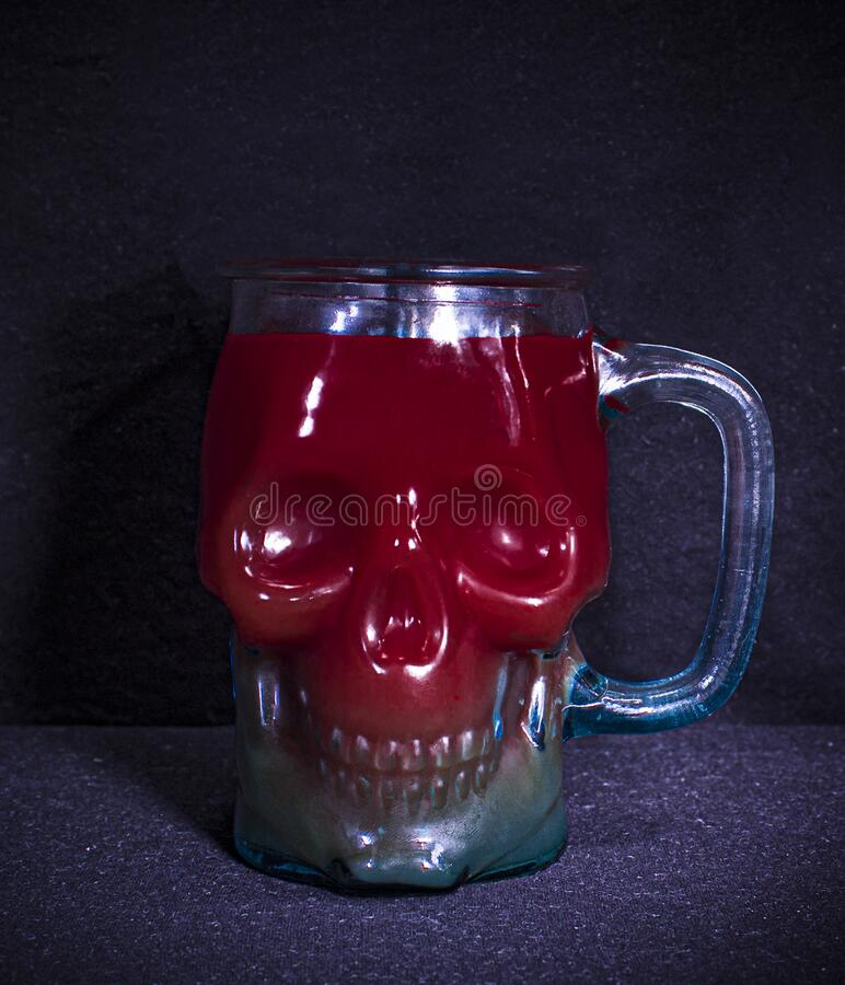 Glass mug in the form of a skull for Halloween.Scary transparent Cup of red and blue color with cocktail. An alcoholic drink simil royalty free stock images