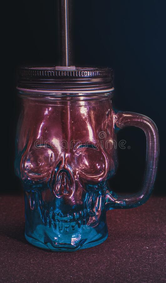Glass mug in the form of a skull for Halloween.Scary transparent Cup of red and blue with a lid, a straw and a cocktail. royalty free stock photography