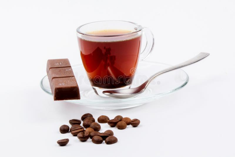 Glass mug full of welded coffee and chocolate bar on a glass plate next to coffee beans on a white background royalty free stock photos