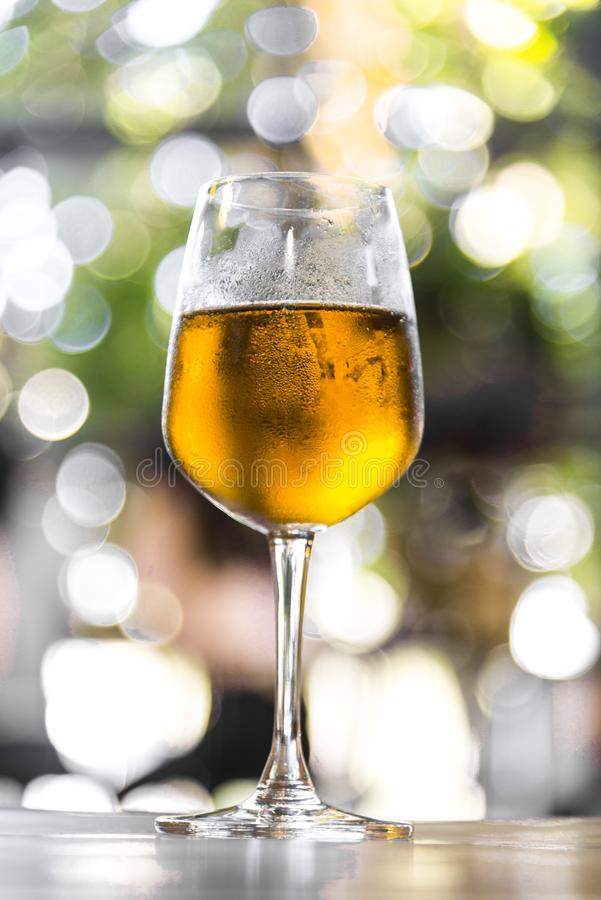Glass of mug golden beer on wood table and green light blured bokeh garden outdoor background stock photo
