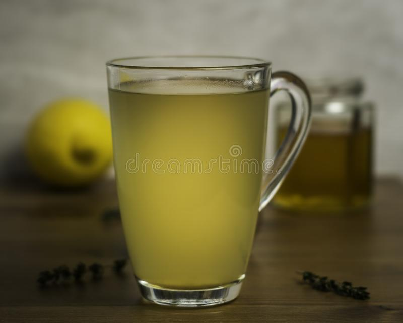 Glass Mug of Hot Lemon, Honey and Ginger Drink with sprigs of Thyme as a cold remedy. Glass Mug of Hot Lemon, Honey and Ginger Drink with sprigs of Thyme to royalty free stock photography
