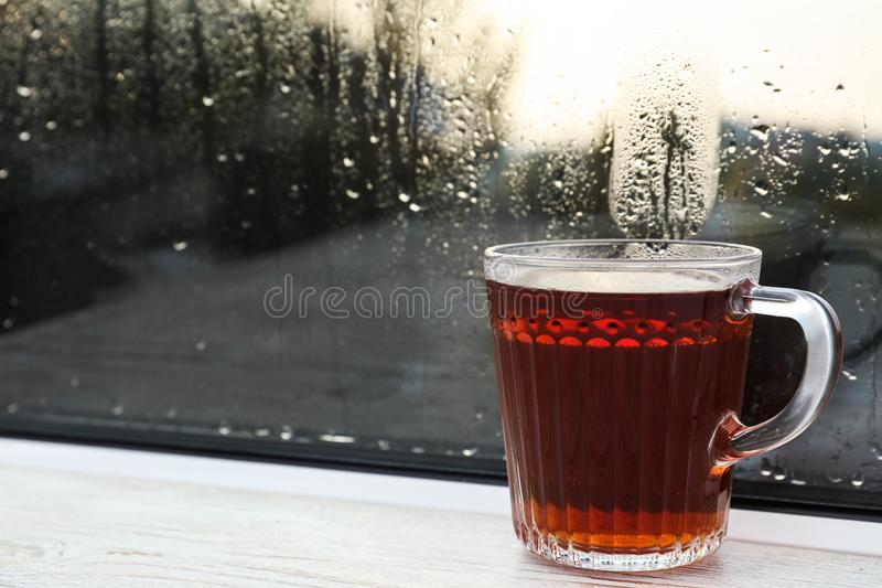 Glass mug of hot tea on white window sill, closeup. Rainy weather. Glass mug of hot tea on white wooden window sill, closeup. Rainy weather royalty free stock images