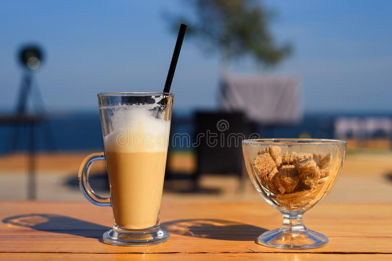 Glass mug with latte and salt shaker and sugar bowl with cane sugar on wooden table royalty free stock photography