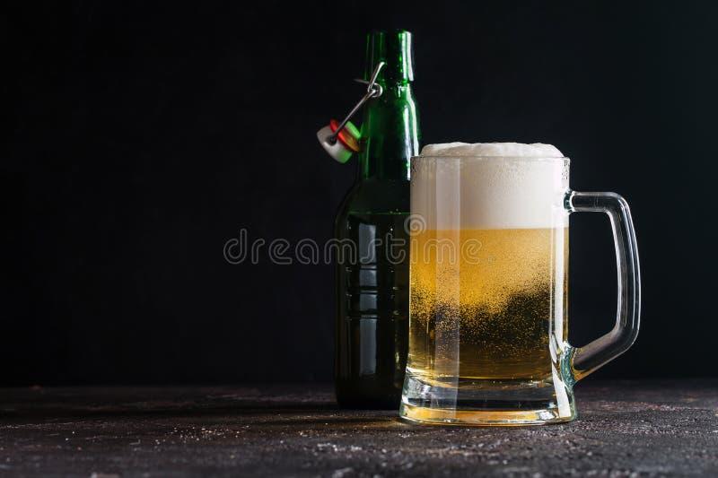 Glass mug of light beer. And bottle on dark background stock image