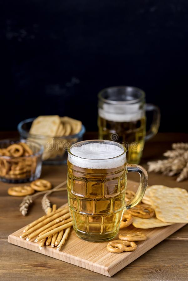 Glass Mug of Tasty Light Beer and Snacks on Wooden Table Pretzel Cracker with Solt Vertical royalty free stock photos