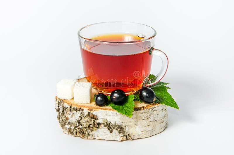 A glass mug of tea with berries of black currant and sugar cubes stands on a birch stump, isolated on a white background stock photo