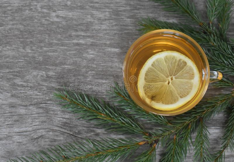 Glass mug with tea with a sprig of spruce on the Board. Drink with lemon on the background of a textured Board and fir twigs royalty free stock image
