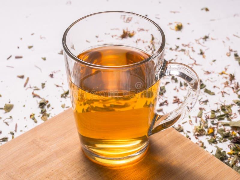 Glass mug with warm herbal tea on wooden board stock photos