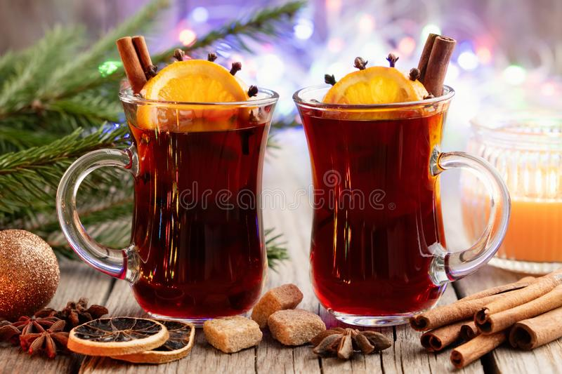 Glass mugs of hot mulled wine, Christmas tree branches and bokeh lights on background. Glass mugs of hot mulled wine with spices and citrus fruits, Christmas royalty free stock photography