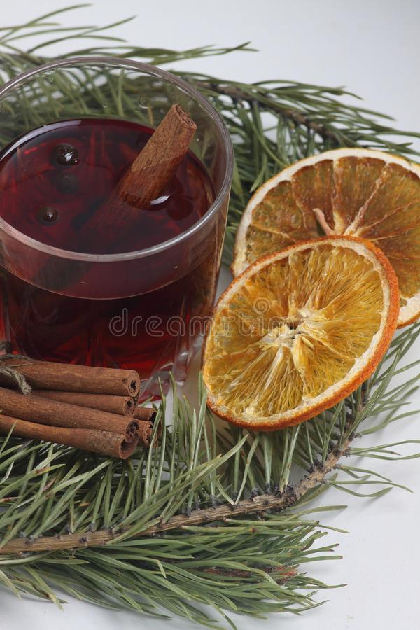 Glass of mulled wine, cinnamon sticks and orange chips with fir bough on white background. Vertical image stock photography
